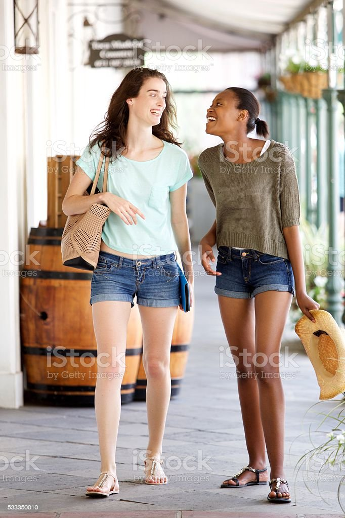Happy young female friends walking together stock photo