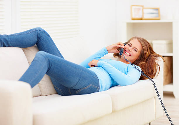 Happy young female lying on a sofa enjoying a phone conversation stock photo
