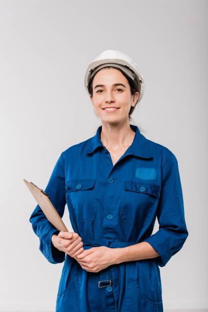 Glückliche junge weibliche Mechanikerin in blauer Arbeitskleidung und Hardhat-Halte-Zwischenablage – Foto