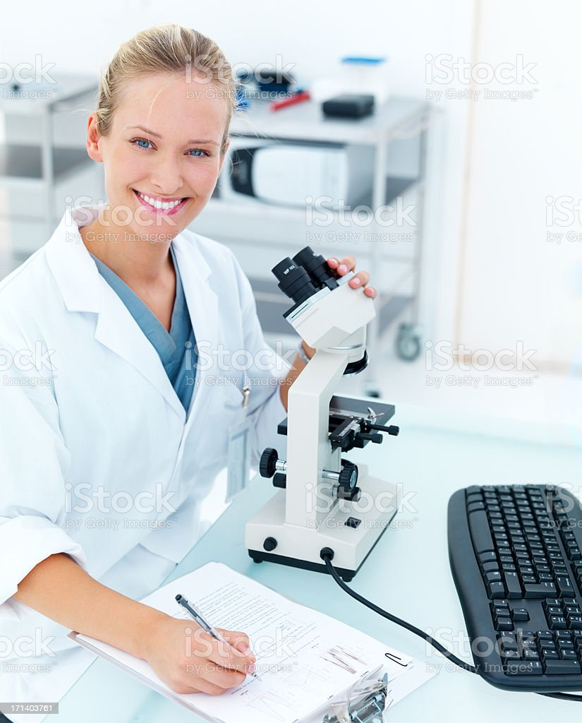 Happy young female researcher using microscope royalty-free stock photo