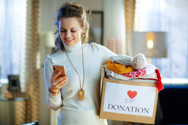 happy young female with donation box with clothes using app stock photo