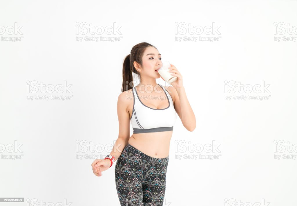 Happy young fitness woman stand and drinking the milk and wear smart watch for tracking heart rate monitor on white background royalty-free stock photo