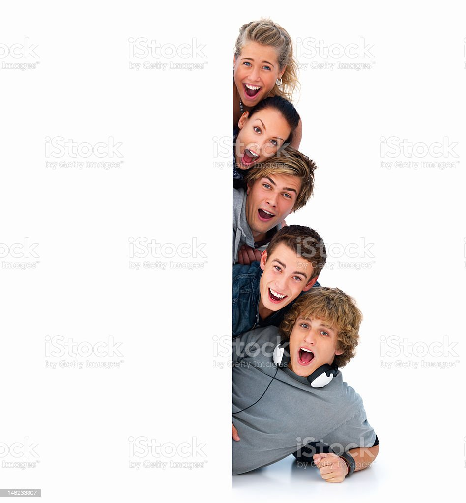 Happy young friends behind a billboard royalty-free stock photo