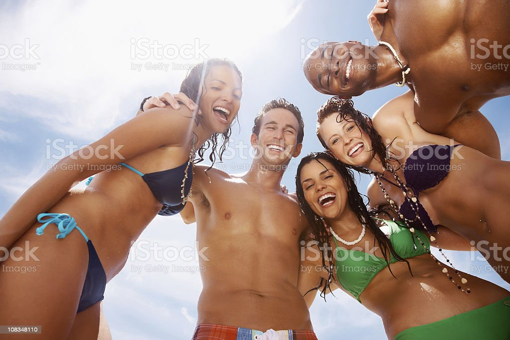 Happy young friends enjoying together on beach against sky royalty-free stock photo