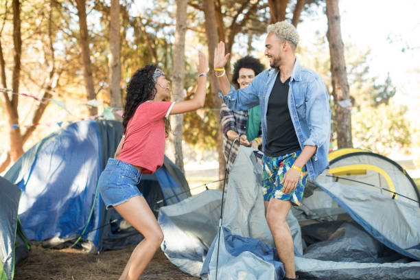 glückliche junge freunde geben hohe fünf beim zelt einrichten - zelt stehhöhe stock-fotos und bilder