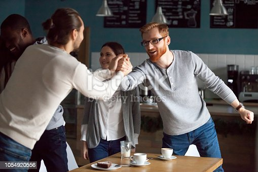 Excited millennial friends greeting, hanging together in café, smiling guy get acquainted with colleague at friendly meeting in coffeeshop, diverse students reunited in cafeteria embracing say hello