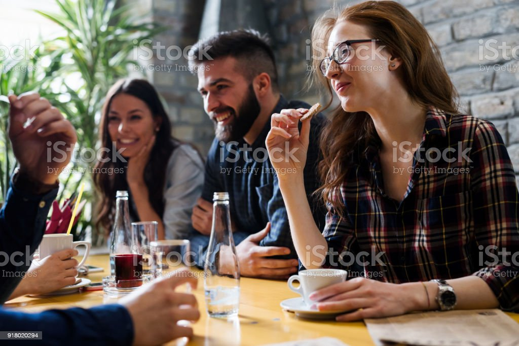 Happy young friends hangout in coffee shop stock photo