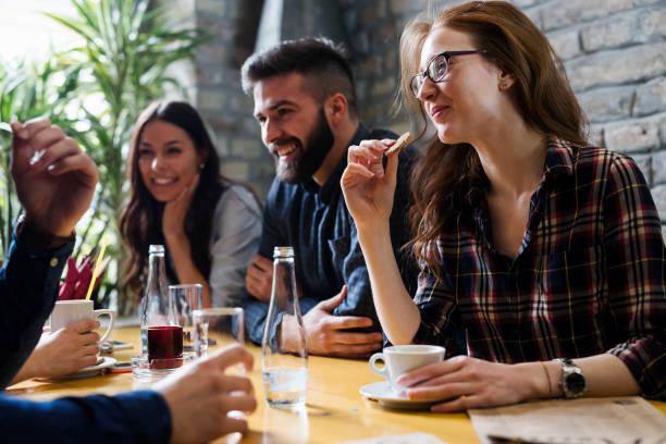 Lugar de reunión de jóvenes amigos feliz en cafetería - foto de stock