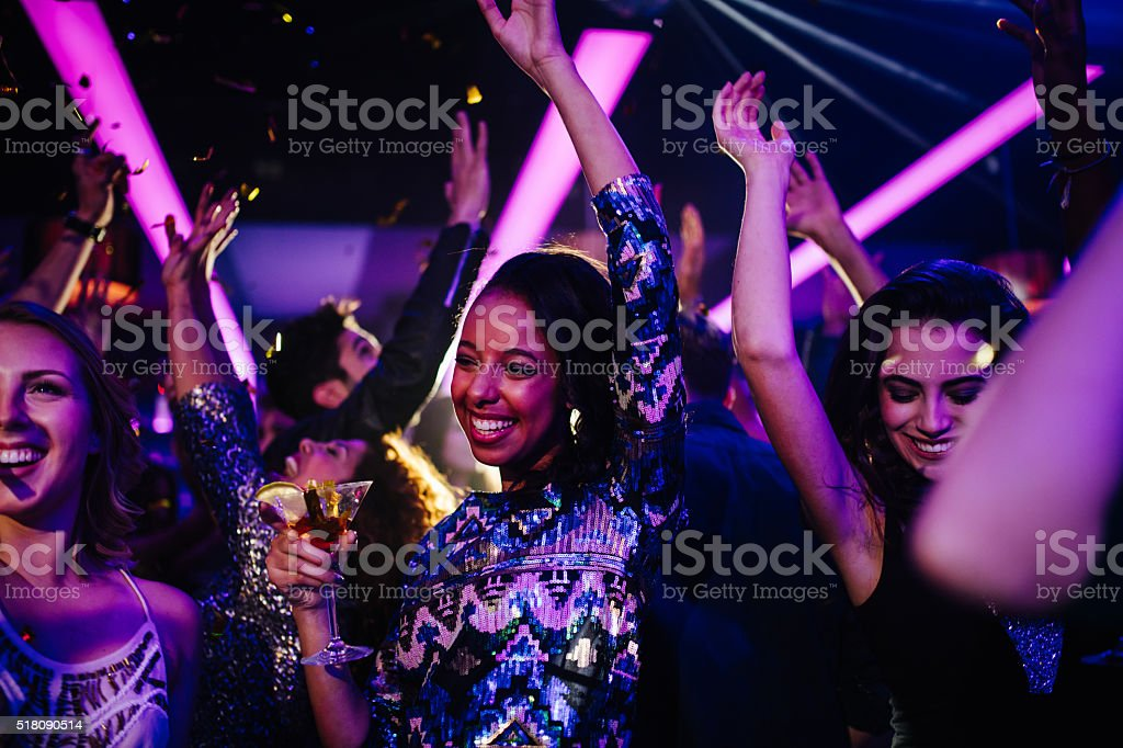 Happy young friends having funny party with confetti and cocktails stock photo