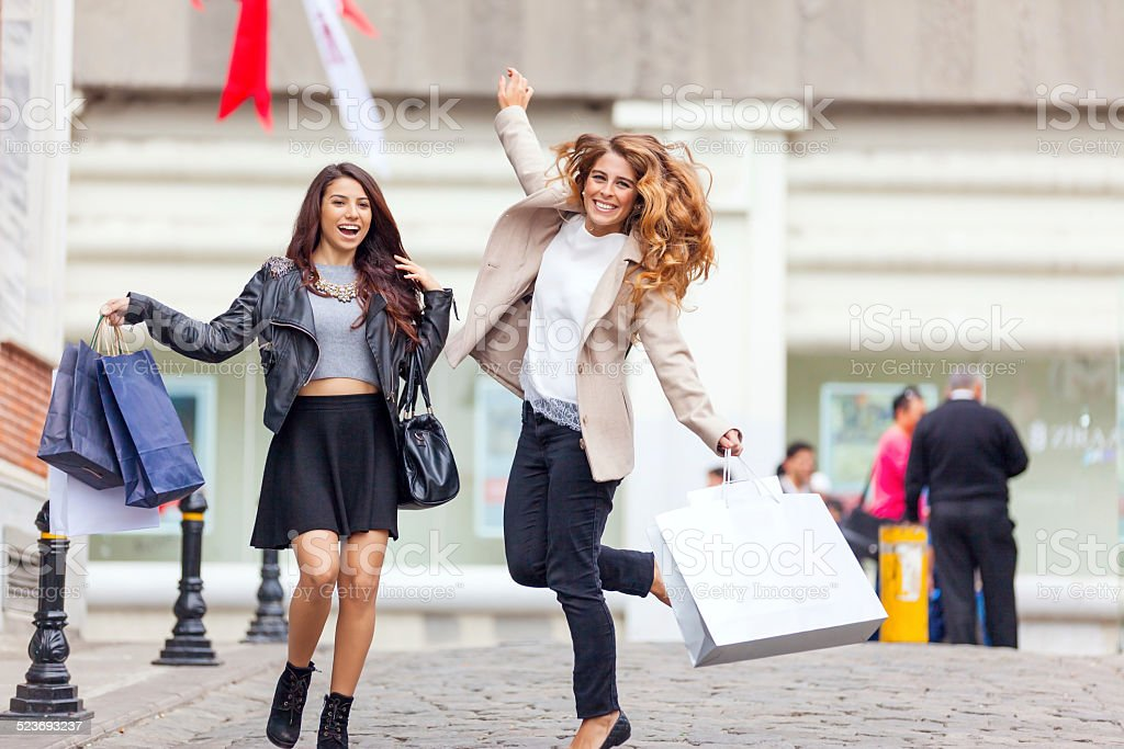 Happy young friends jumping with shopping bags stock photo