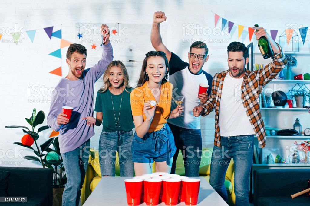 happy young friends looking at smiling girl playing beer pong at home party stock photo