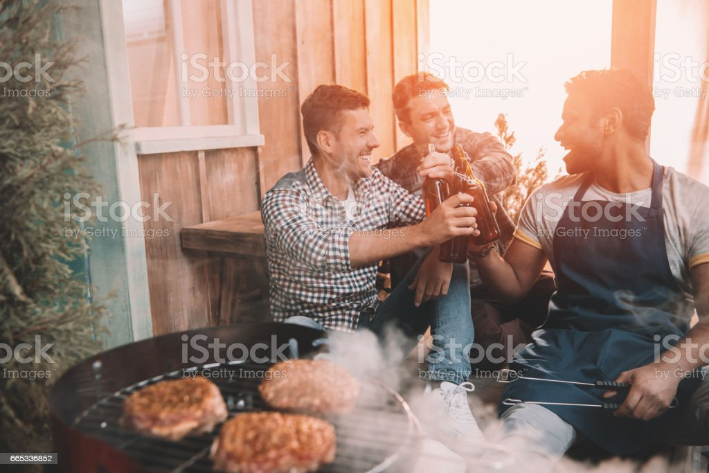 happy young friends making barbecue and drinking beer on porch with back light stock photo