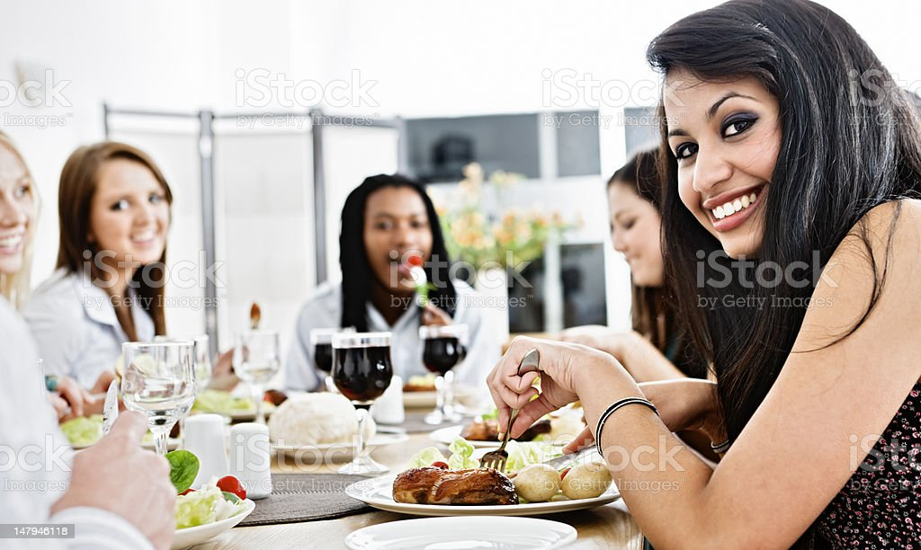 Happy young friends or colleagues dine together and smile royalty-free stock photo