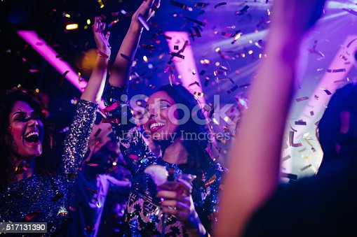 Happy young adult multi-ethnic friends having a funny party with drinks and confetti on the dance floor of a night club