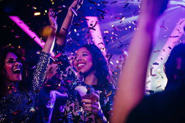 Happy young friends partying with drinks and confetti in nightclub stock photo