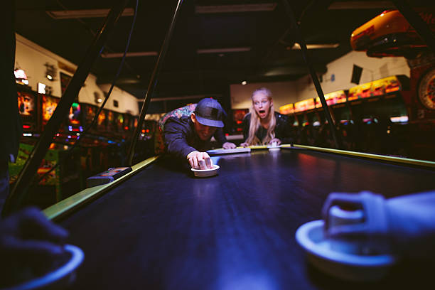 Happy young friends playing air hockey at amusement park - foto de acervo