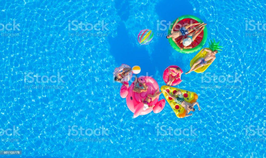 ANTENA: Felizes amigos jovens jogando biribol fun boias na piscina - foto de acervo