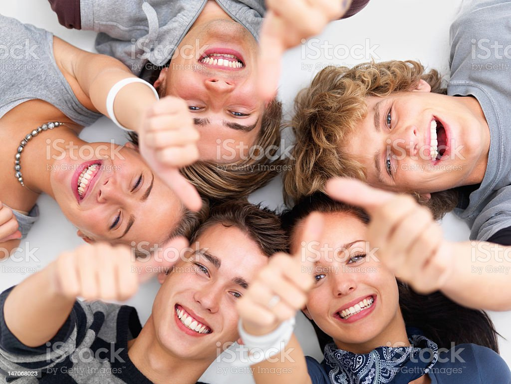 Happy young friends showing thumbs up sign royalty-free stock photo