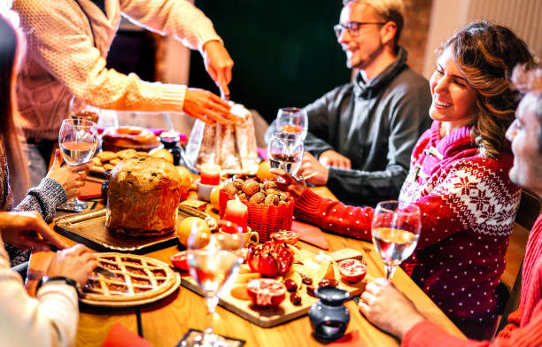 Happy young friends tasting Christmas sweet food having fun at home supper party - Winter friendship concept with millenial people enjoying new year's eve dinner eating together - Warm filter stock photo