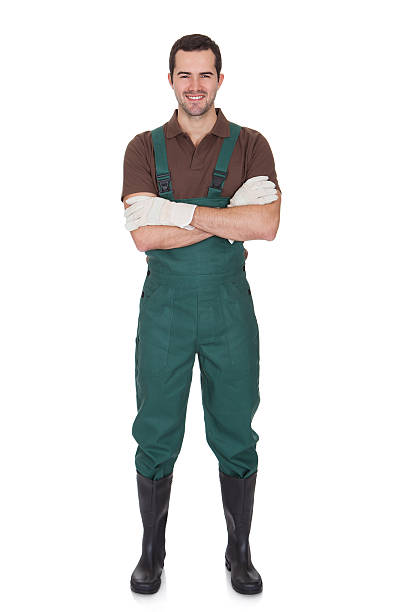 Happy young gardener in dungarees Happy young gardener in dungarees. Isolated on white bib overalls boy stock pictures, royalty-free photos & images