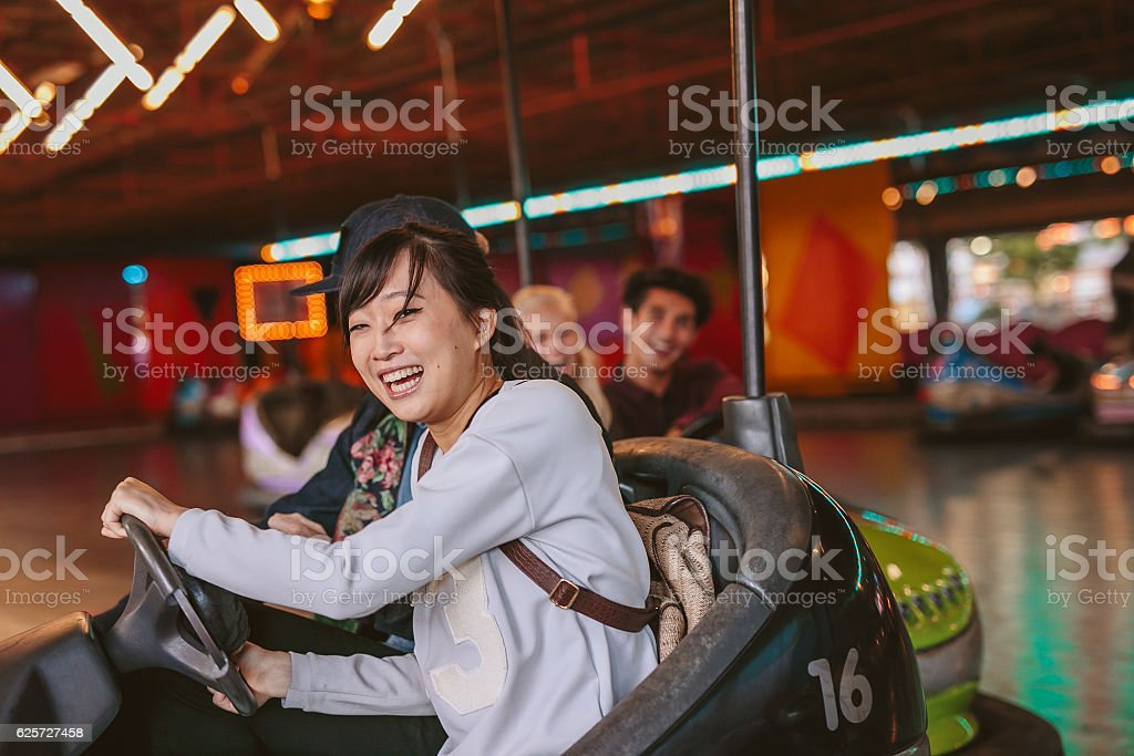 Happy young girl driving a bumper car stock photo