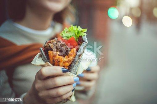 Cute teenage girl eating kebab, shwarma  or roll outdoors