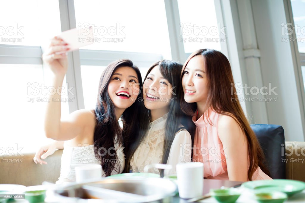 happy young girl friend taking selfie together in restaurant zbiór zdjęć royalty-free