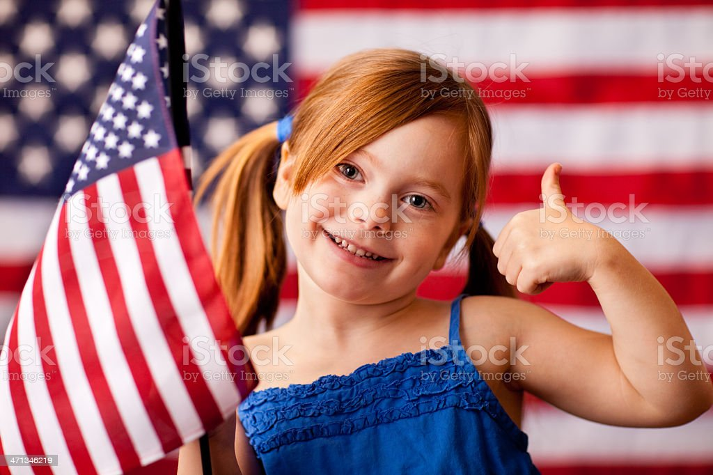 Happy, Young Girl Giving Thumbs Up and Holding American Flag royalty-free stock photo