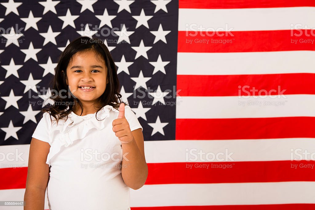 Happy, Young Girl Giving Thumbs Up by American Flag stock photo