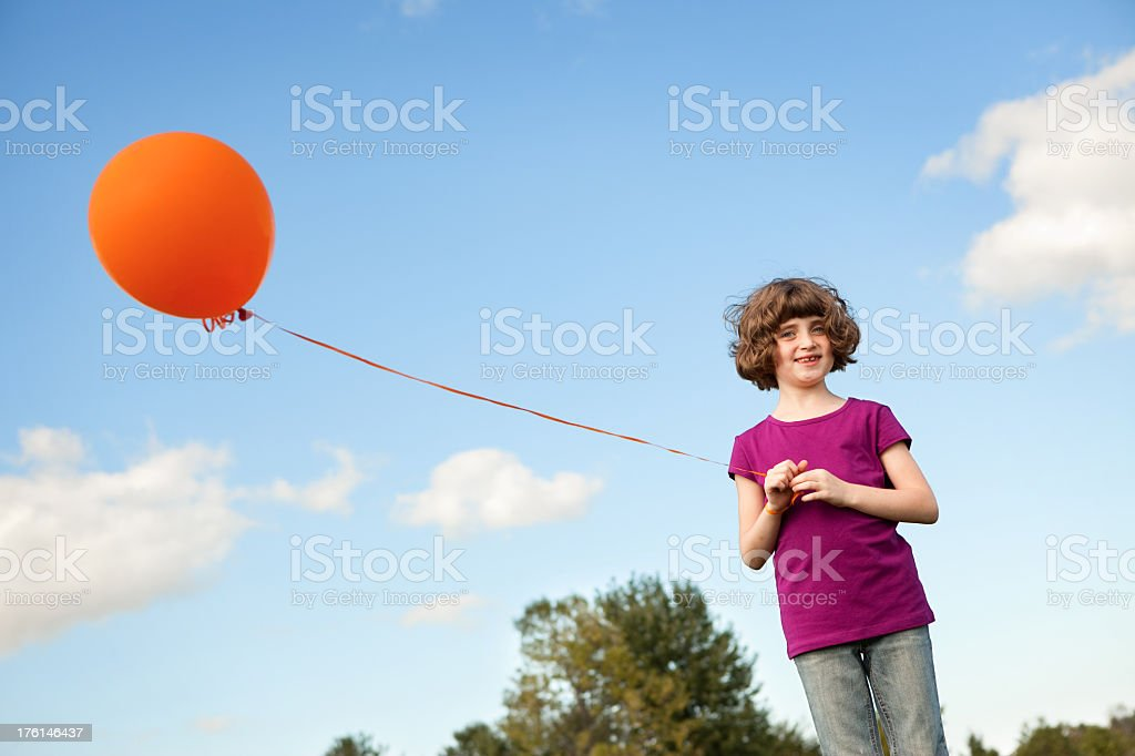 Happy Young Girl Holding a Balloon Outside royalty-free stock photo