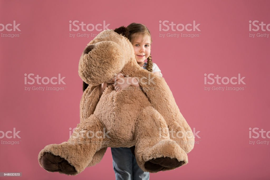 Portrait of happy young girl holding big teddy bear