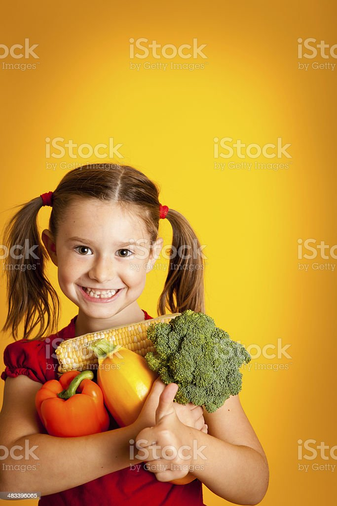 Happy Young Girl Holding Orange Bell Pepper, Broccoli, Squash, Corn royalty-free stock photo