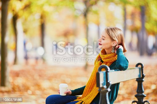 Happy young girl in yellow scarf with coffee to go walking in autumn park on a bright fall day