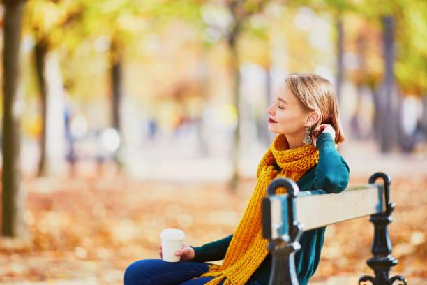 feliz joven en bufanda amarilla caminando en el parque otoño - moda parisina fotografías e imágenes de stock