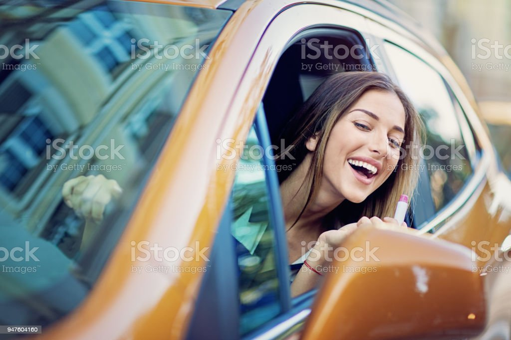 Jovem feliz é colocar batom no trânsito - foto de acervo