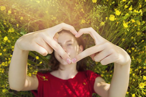 Happy young girl lies in the dense green grass in the park and shows hands a heart shape