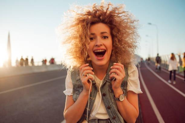 Feliz joven en la calle. Hermosa rubia con auriculares y teléfonos inteligentes. - foto de stock