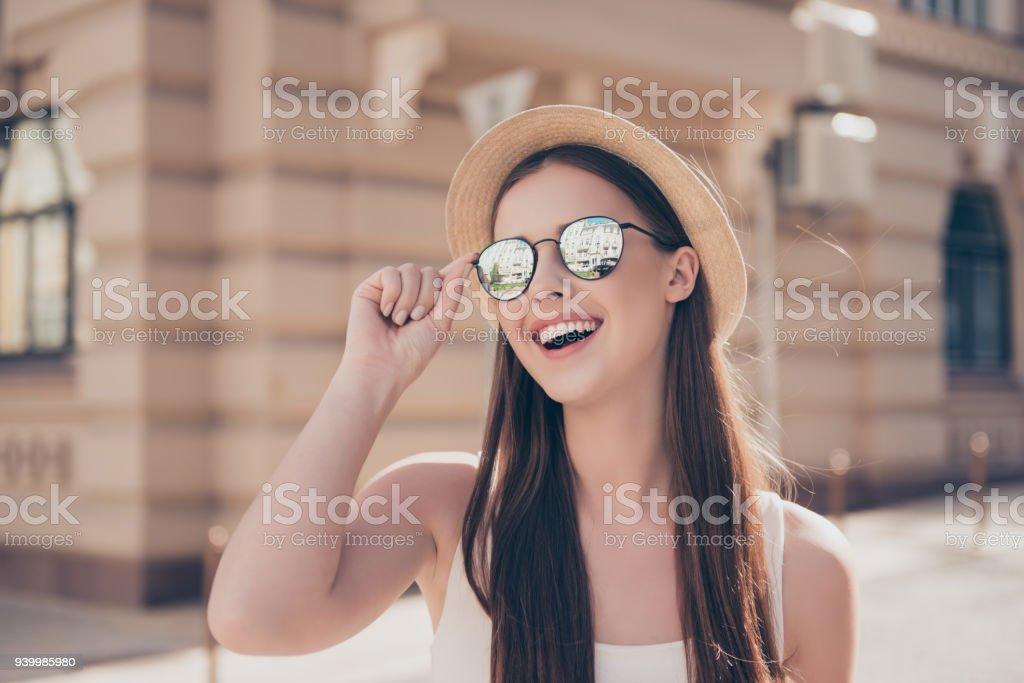 Heureuse jeune fille en vacances. Elle tient dans un élégant chapeau et des  lunettes de 5fd4a4d813dc