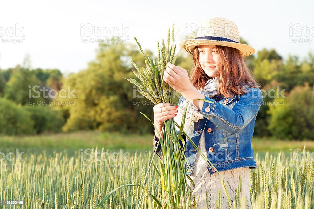 Happy young girl picking stems on wheat field. stock photo
