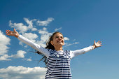 Happy young girl holding her hands up on a sky background