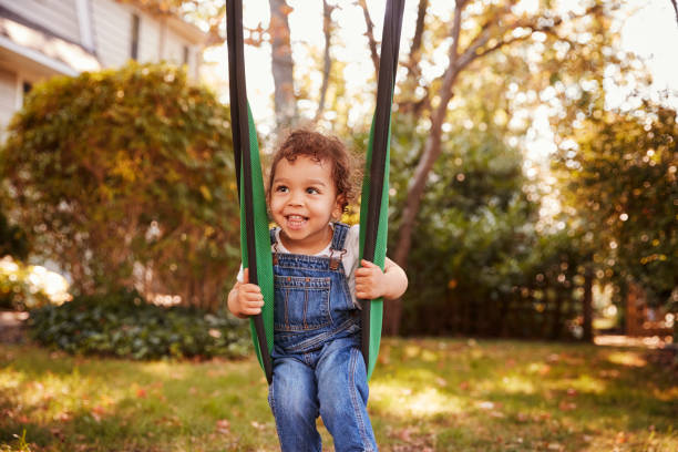 Happy Young Girl Playing On Garden Swing stock photo
