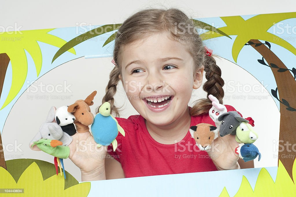 Happy young girl playing with finger puppet animals royalty-free stock photo