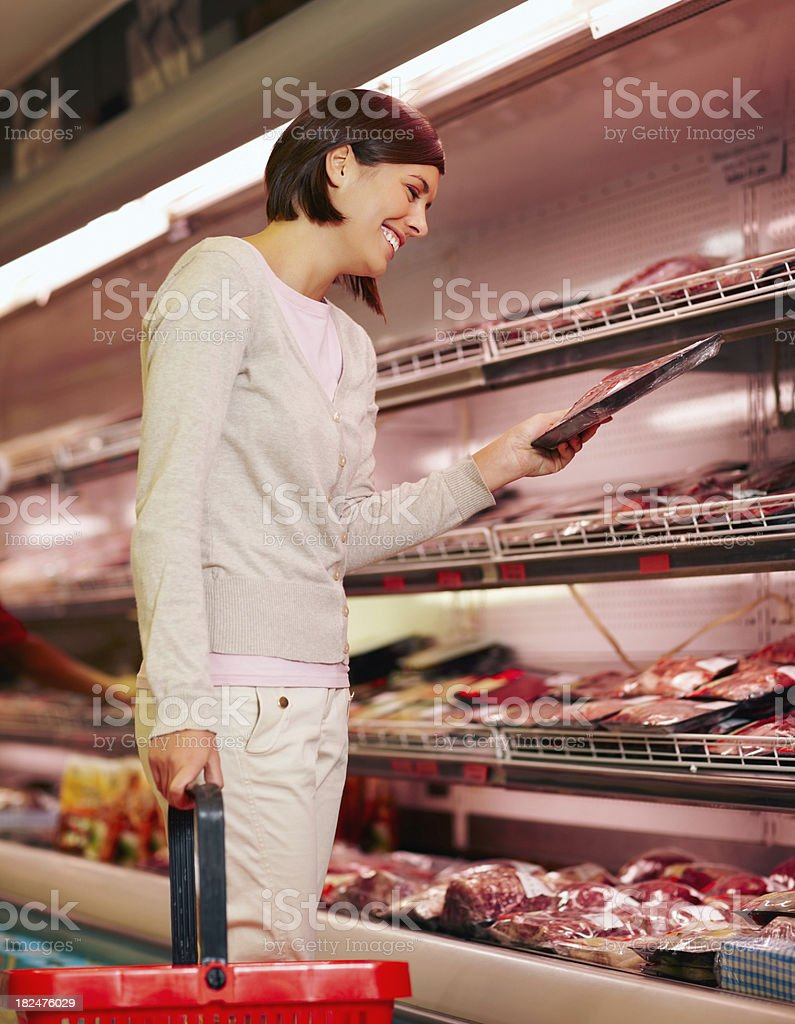 Happy young girl purchasing a packet of meat royalty-free stock photo