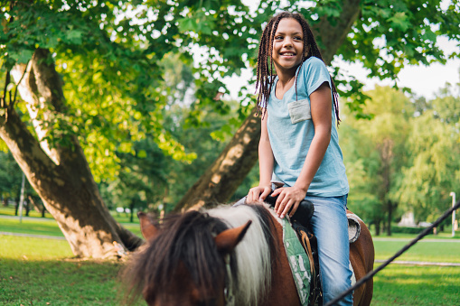 Happy young girl riding a horse