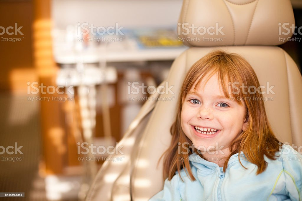 Happy Young Girl Sitting in Dental Chair at Dentist Office stock photo
