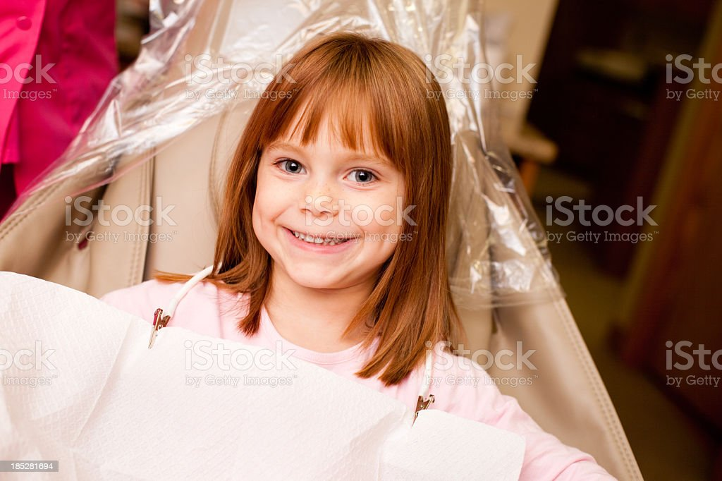 Happy Young Girl Sitting in Dental Chair at Dentist Office royalty-free stock photo