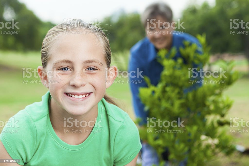 Happy young girl smiling after planting tree royalty-free stock photo