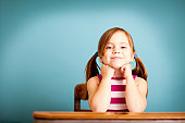 Color photo of a happy, young girl student sitting in a school desk on blue background.
