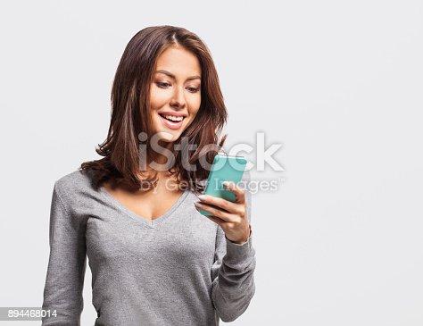 istock Happy young girl using smart phone 894468014