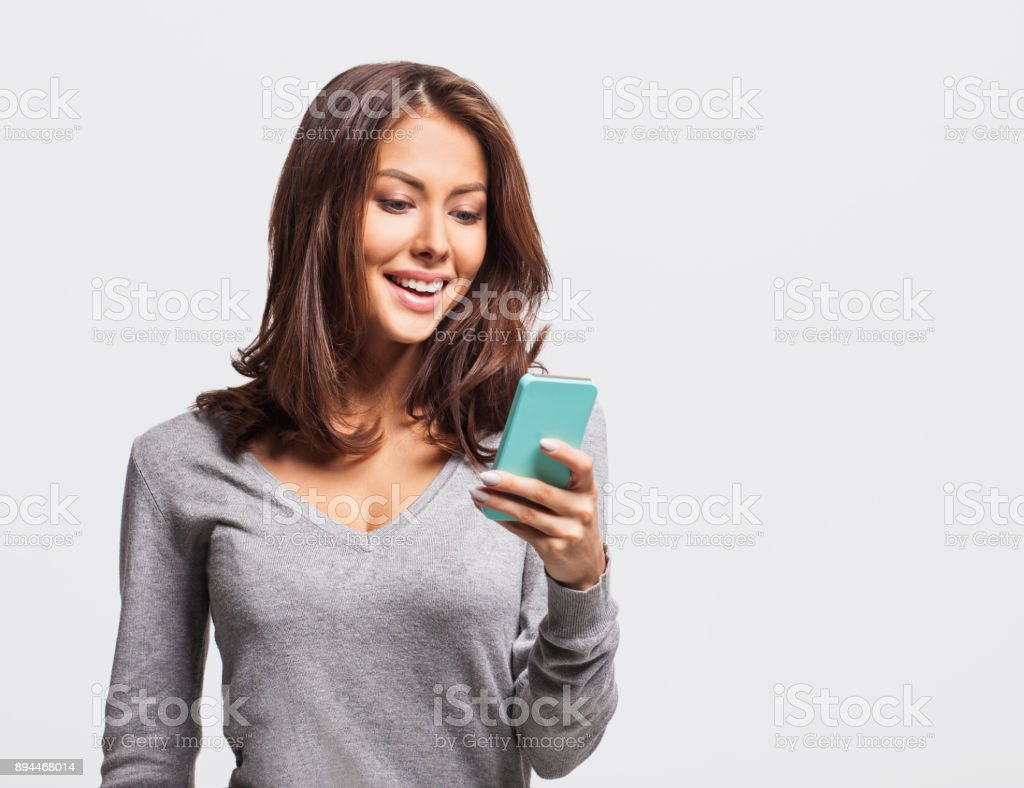 Happy young girl using smart phone stock photo